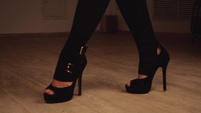 Woman`s legs in black stockings and stipper shoes move while dancing. Woman`s legs in black stockings and stipper shoes move while dancing in studio stock video