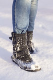 Woman`s legs with blue jeans and black shoes in a snow Royalty Free Stock Images