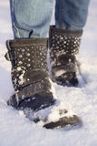 Woman`s legs with blue jeans and black shoes in a snow Royalty Free Stock Photos