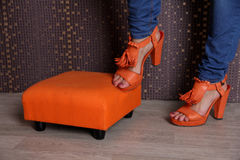 Woman's legs in bright orange shoes Stock Image