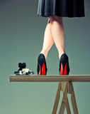 Woman's legs and the camera. Woman legs in shoes with red soles and the camera on a table Royalty Free Stock Photography