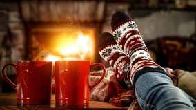 Woman`s legs with christmas socks and red mugs of coffee or tea and home interior with fireplace and dark wall background.