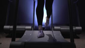 Woman s legs in white sneakers and leggings running on treadmill in gym