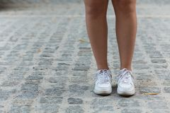 Woman's legs. Close-up picture of young woman's legs in the street. Woman in white training shoes walking stock images