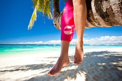 Woman's legs closeup, sitting on coconut palm Royalty Free Stock Photos