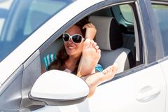 Woman's legs dangling out a car Royalty Free Stock Images