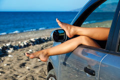 Woman's legs dangling out a car window Royalty Free Stock Image