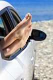 Woman's legs dangling out a car window Stock Image