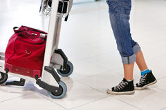 Woman's legs and feet with luggage car. Close up of woman's legs and feet with luggage cart with bag Royalty Free Stock Image