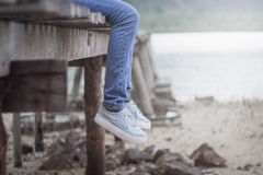 Woman's legs hanging on the old wooden bridge. The lonely tone vintage style like no other. Royalty Free Stock Images