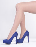 Woman's Legs in Heels. Close Up of Woman's Legs in Blue High Heels  Sitting Against a White Background Stock Image