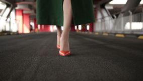 Woman`s legs in high heel shoes walking on road. Closeup beautiful female wearing orange high heel shoes in emerald green coat walking in covered parking garage stock video
