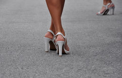 Woman's legs in high heels. Woman's legs in white high heels on the street Royalty Free Stock Photo