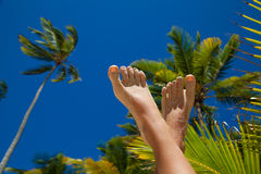 Woman's legs on holiday background. Beautiful woman legs on the Caribbean beach. Woman's Bare Feet with fashion pedicure over palms background. Vacation Concept Stock Image