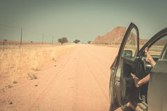 Woman`s legs leaning out from car standing on gravel road in the Namib desert, Namib Naukluft National Park, main travel destinati. On in Namibia, Africa. Toned Stock Photo
