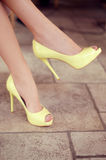 Woman's legs in light yellow open-toe pumps. Woman sitting in a Royalty Free Stock Photos