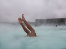 Woman's legs looking out of water in Blue Lagoon in Iceland Stock Photography