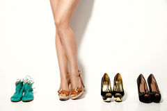 Woman's legs and many shoes over white background Stock Image