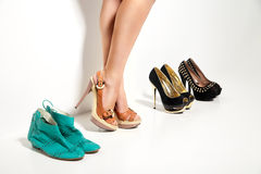 Woman's legs and many shoes over white background Stock Photography