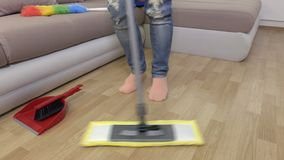 Woman`s legs and mop moving in music rhythm. In room stock video
