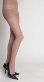 Woman's Legs in Nude Hose Against White Backgroun Stock Photography