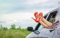 Woman's legs out of the car. Royalty Free Stock Image