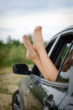 Woman's legs out of the car. Stock Photos