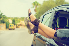 Woman's legs out of the car window. Stock Photo