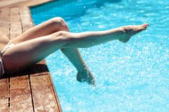 Woman`s legs over pool water Stock Images