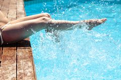 Woman`s legs over pool water Stock Photo