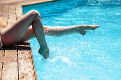 Woman`s legs over pool water Royalty Free Stock Photography