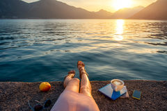 Woman's legs on the pier at sunset. Woman's legs on the pier with apple, coffee cup and books at beautiful sunset Stock Image