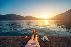 Woman's legs on the pier at sunset. Woman's legs on the pier with apple, coffee cup and books at beautiful sunset Royalty Free Stock Images