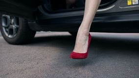 Woman`s legs in red high heels stepping out of car stock video footage