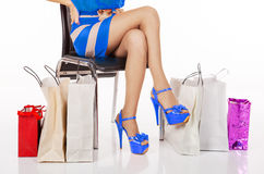 Woman`s legs resting on a chair with shopping Royalty Free Stock Image