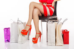 Woman's legs resting on a chair with shopping Royalty Free Stock Photos
