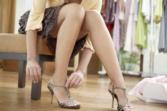 Woman's Legs with Shoes. Close up of a young sophisticated woman tryin on new shoes in a fashion store stock image