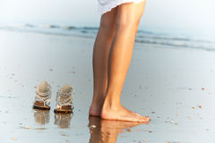 Woman's legs and shoes with ocean Stock Image