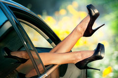 Woman's legs in shoes out in car window Stock Photo