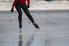 Woman`s legs on skates ice rink - winter sport at sunny day Stock Images