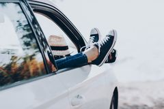 Woman`s legs in sneakers in the window car with straw hat. Girl in jeans in the car with her legs crossed. royalty free stock photo