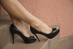 Woman's legs on stairs wearing black high heels. Royalty Free Stock Image