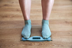 Woman's legs standing on the scales Royalty Free Stock Image