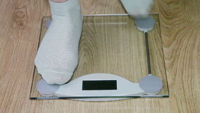 Woman's legs standing on the scales stock video