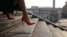Woman`s legs stepping down on stairway in city stock video