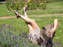 A woman's legs thrown sky. Beautiful woman lying on the green grass in summer day Royalty Free Stock Photos