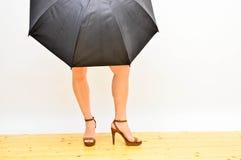 Woman`s legs under umbrella. Woman`s legs on high heels  under black umbrella on white background Stock Photos