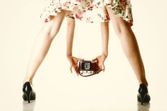 Woman's legs and vintage camera Stock Photo