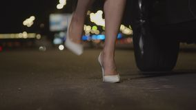 Woman`s legs waiting impatiently near car at night stock video