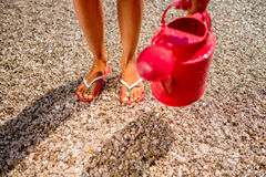 Woman's legs with watering can on the beach Royalty Free Stock Images